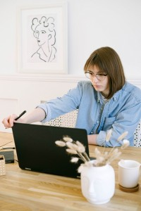 a designer looks studiously down at her laptop with a pen in her hand