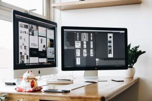 A modern dual-screen desktop computer running photoshop, in a modern office setting.