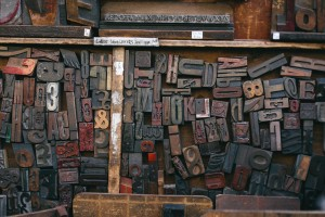 A Selection of various vintage wooden font blocks, as used with an old-style printing press, in a storage tray